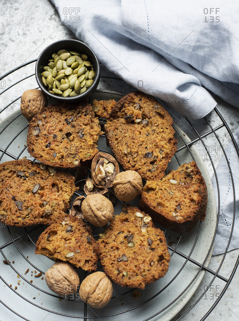 Still life of walnut and pumpkin seed cake sliced on cooling rack, overhead view
