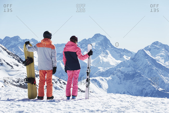 Teenage boy snowboarder with sister skier looking out from snow covered mountain top, rear view,  Alpe-dHuez, Rhone-Alpes, France
