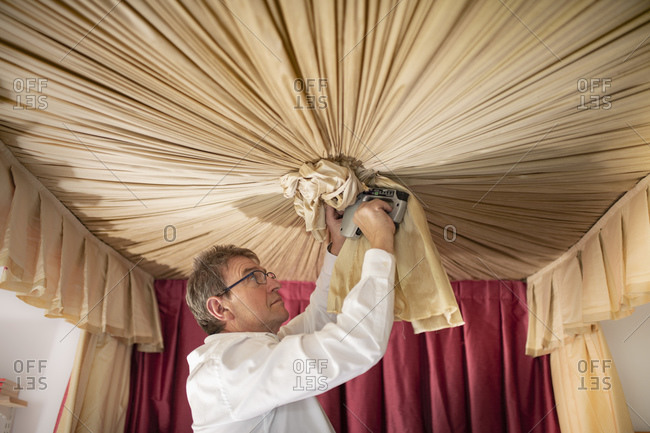 Curtain fitter making Ruche' on canopy of four poster bed