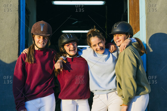 Portrait of cheerful female jockeys standing together against stable on sunny day
