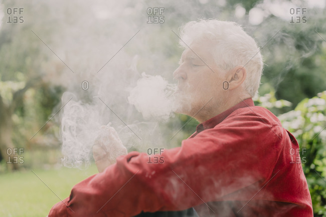 Senior man sitting amidst smoke at orchard
