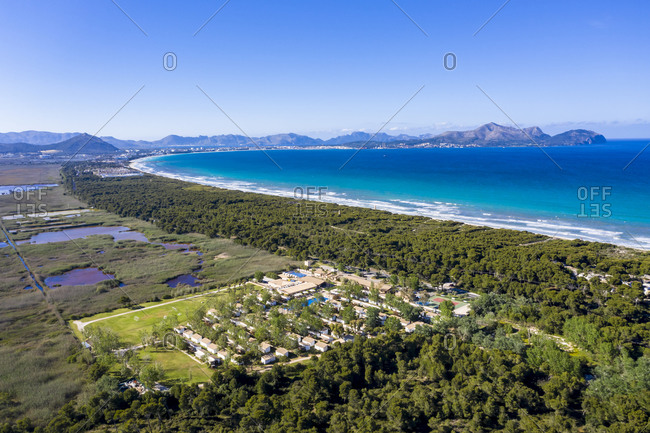Spain- Balearic Islands- Mallorca- Can Picafort- Helicopter view of tourist resort and forested coastline in summer