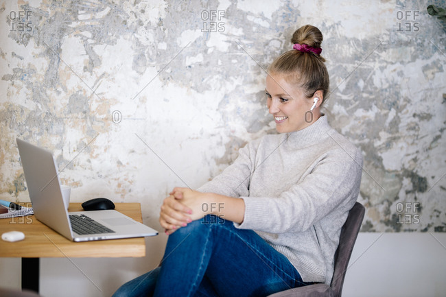Smiling blond woman sitting on armchair at home having video chat with laptop and earphones
