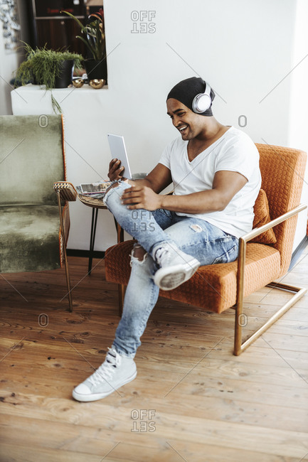 Laughing man using mini tablet and headphones at home