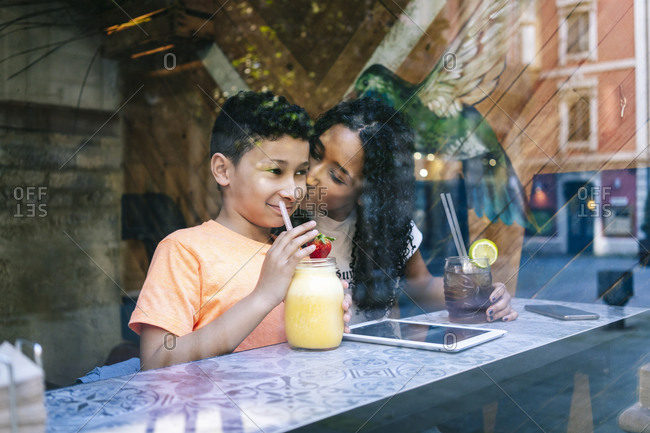 Young woman kissing son drinking smoothie seen through restaurant window