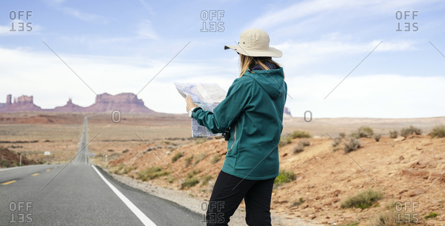 Female tourist reading map while standing on roadside against sky- Monument Valley Tribal Park- Utah- USA