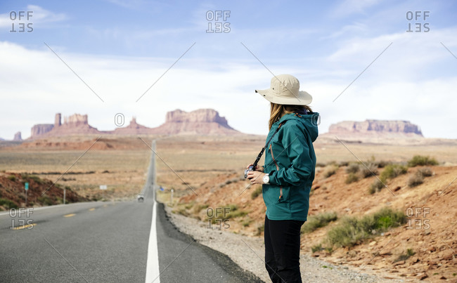 Side view of female tourist standing with camera on roadside against sky- Monument Valley Tribal Park- Utah- USA