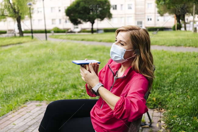 Woman with surgical mask using  hands-free telephone sitting on bench