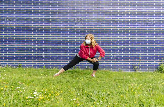 Woman with surgical mask stretching her leg on meadow