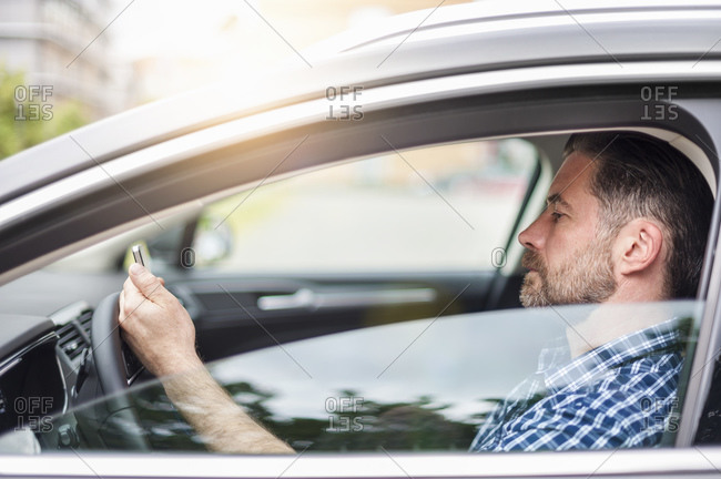 Side view of handsome man using mobile phone while sitting in car