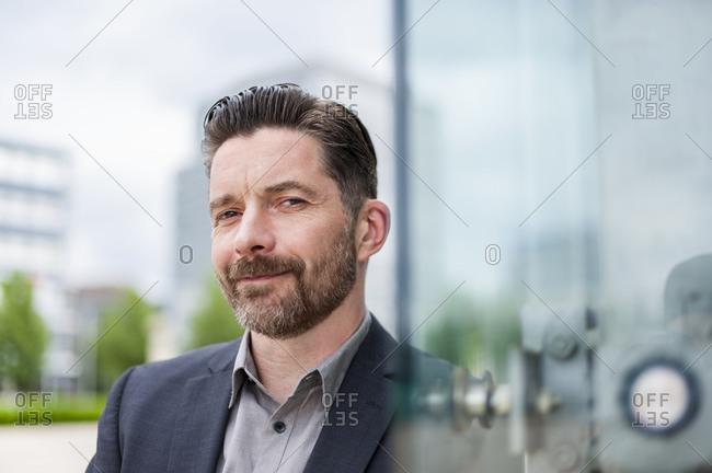 Portrait of handsome businessman standing outside office building