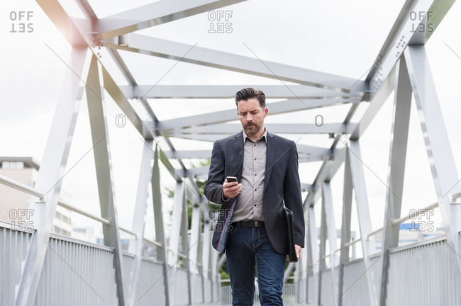 Confident handsome businessman using smart phone while walking on footbridge in city