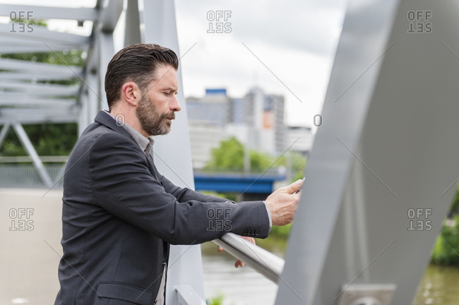 Side view of handsome bearded entrepreneur standing on footbridge with mobile phone in city
