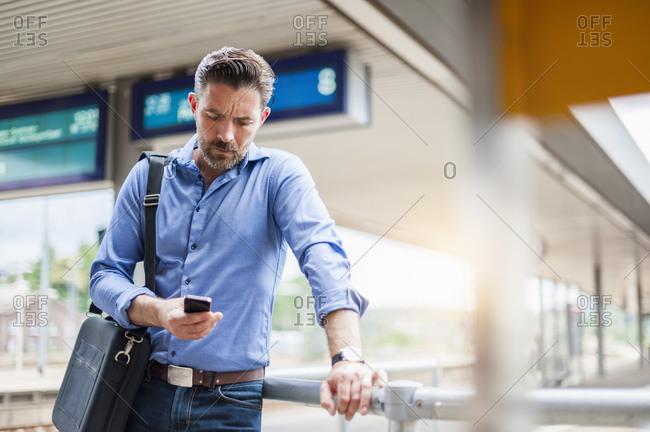 Mature businessman using smart phone while waiting at railroad station