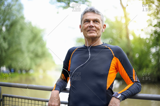 Retired senior man looking away while smiling against railing in park