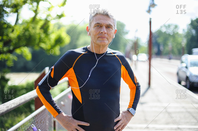 Portrait of confident senior man in sports clothing standing with hands on hip during sunny day