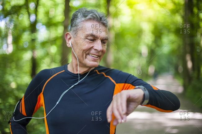 Smiling senior man checking time while walking at park