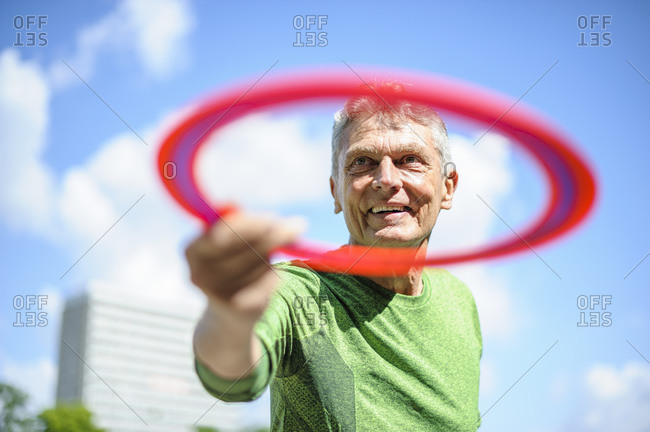 Smiling active senior man holding plastic disc at park against sky on sunny day