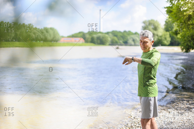 Active elderly man checking time while standing at riverbank on sunny day