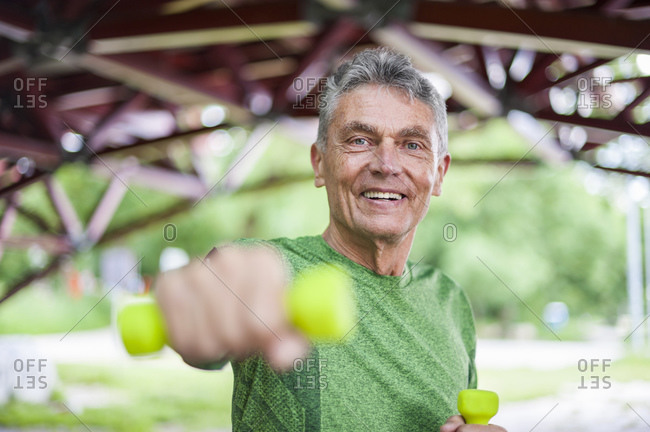 Portrait of smiling senior man exercising with dumbbells while standing at gazebo in park