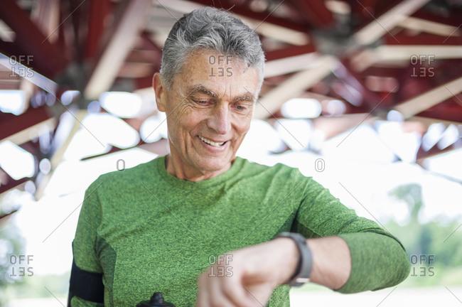 Smiling elderly man checking time while standing at gazebo in park