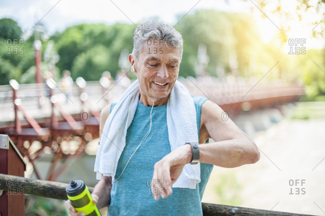 Smiling active senior man looking at smart watch while standing in park