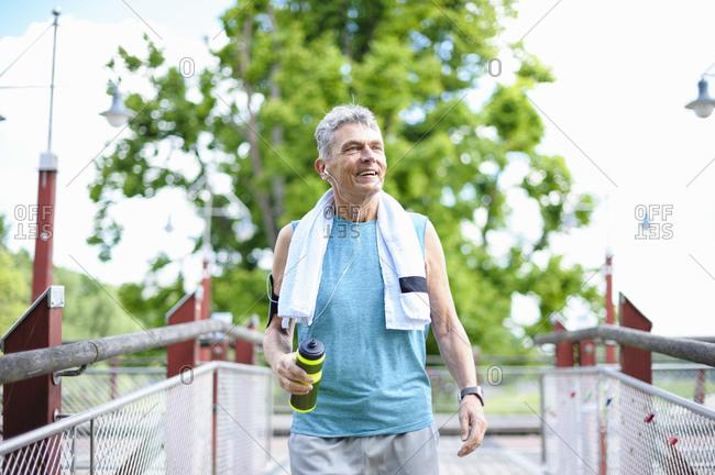 Smiling senior man holding water bottle while walking on footbridge at park