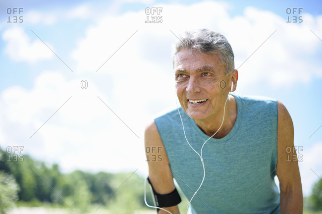 Low angle view of exhausted senior man at park against sky on sunny day