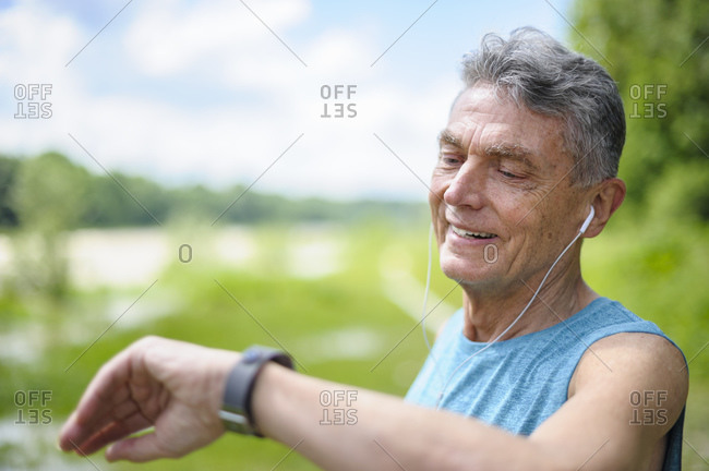 Smiling senior man checking time at park on sunny day