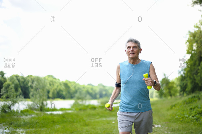Active senior man jogging with dumbbells at riverbank against clear sky