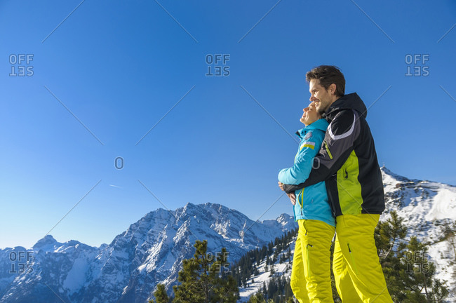 Smiling man hugging woman from behind while standing against clear blue sky