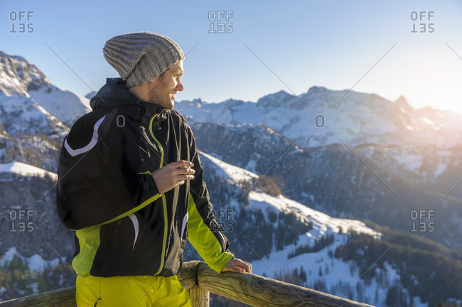 Man standing by railing while looking at snowcapped mountains against sky