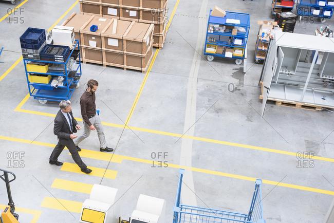 Two businessmen walking on factory shop floor