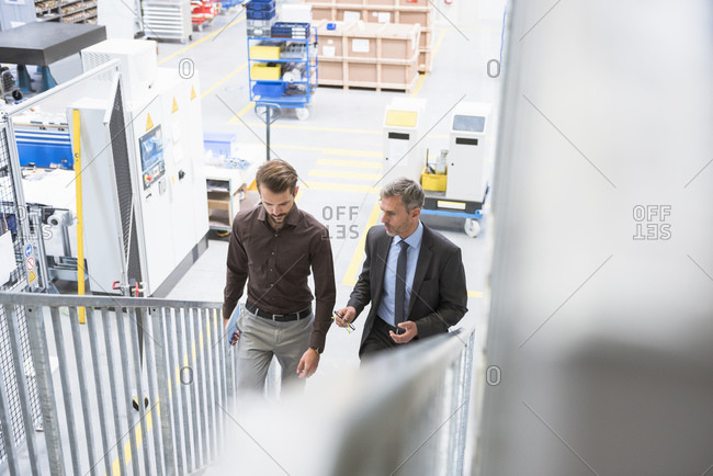 Two businessmen walking up stairs in a factory