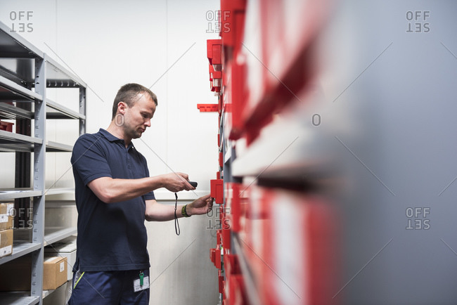Man in storehouse of a factory scanning goods