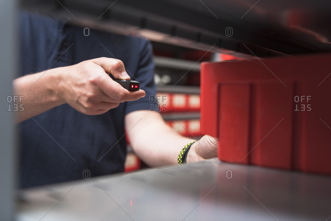 Close-up of man in storehouse of a factory using small scanner