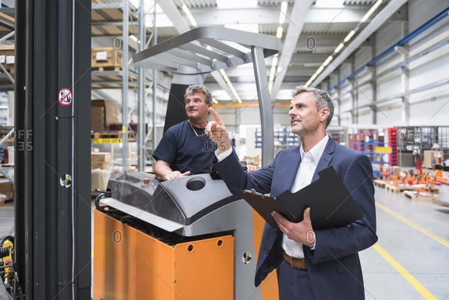 Businessman instructing worker on forklift in high rack warehouse