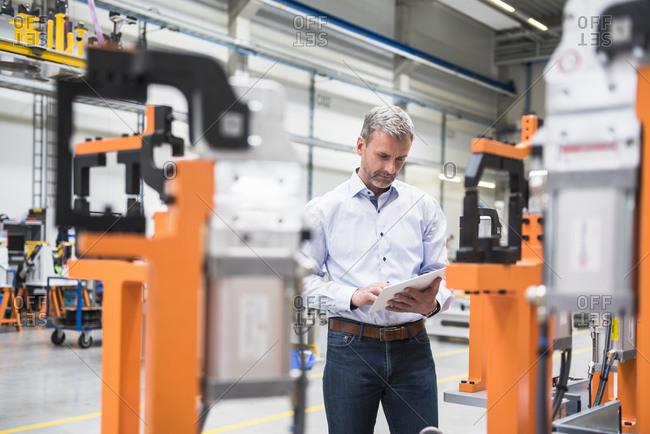 Mature man using tablet on factory shop floor