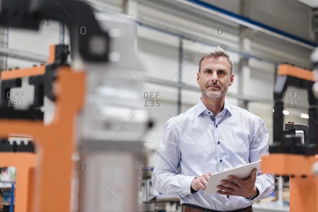 Portrait of mature man using tablet on factory shop floor