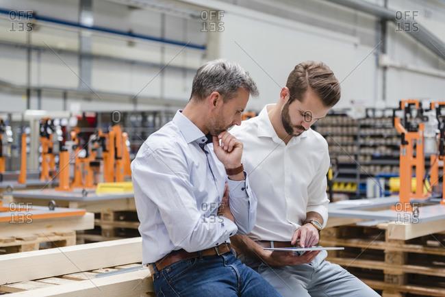 Two men sharing tablet on factory shop floor