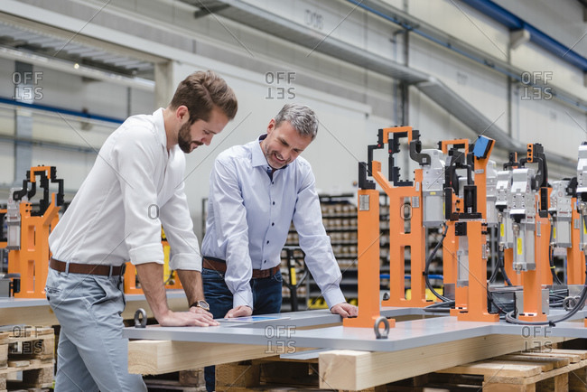 Two men looking at tablet on factory shop floor