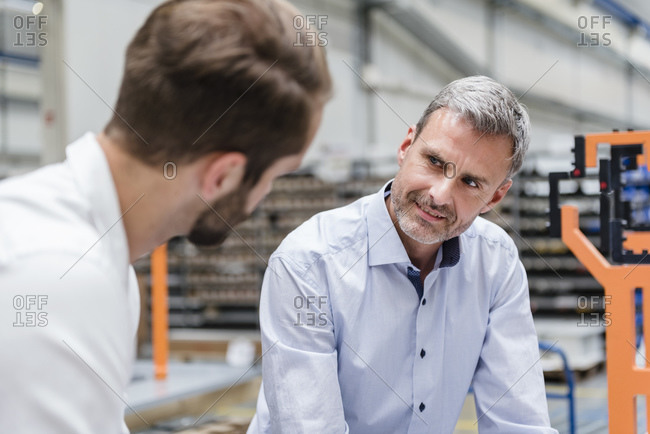 Portrait of mature man looking at colleague on factory shop floor