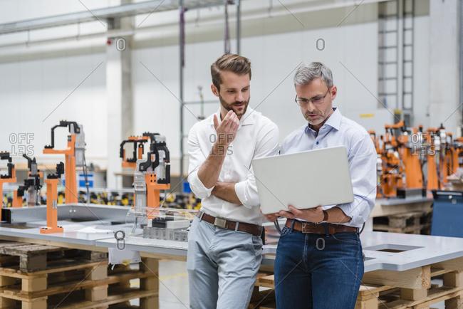 Two men using laptop on factory shop floor