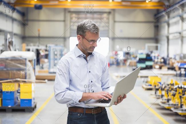 Mature man using laptop on factory shop floor