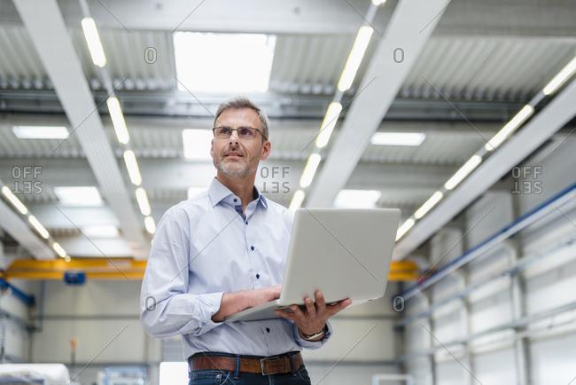Mature man holding laptop on factory shop floor