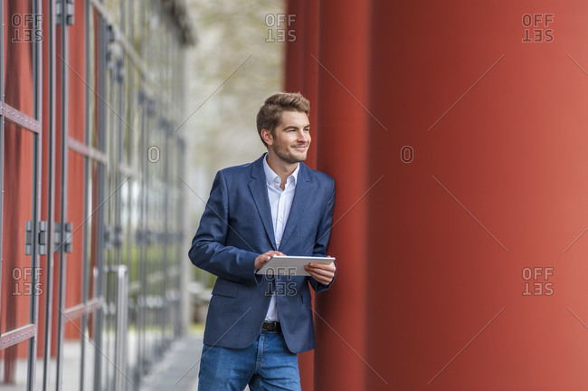 Young businessman using tablet outside a building