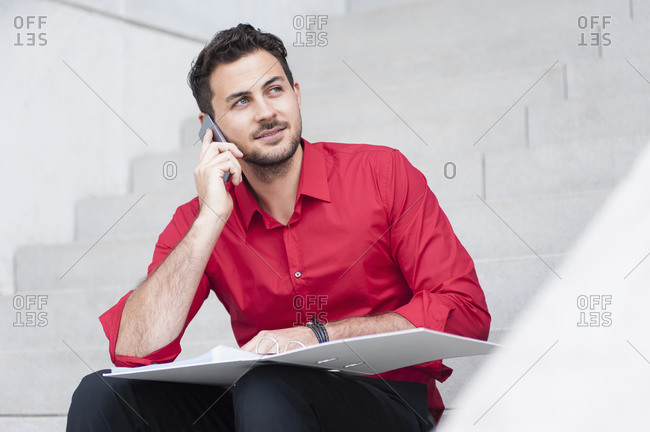 Smiling businessman calling with folder sitting on the stairs