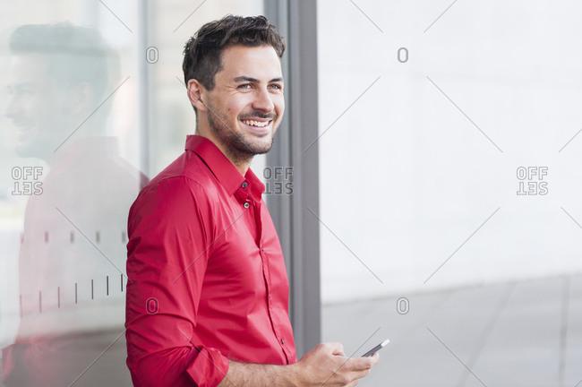 Smiling businessman using smartphone outside