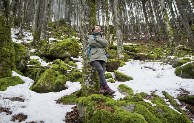 Woman leaning on beech tree in Northern Black Forest with snow remnants during springtime