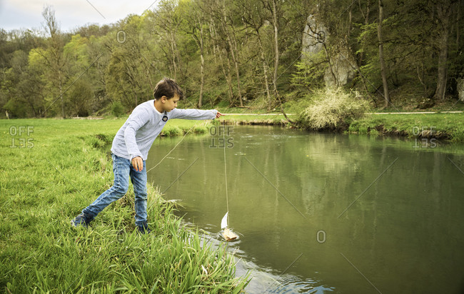 Boy holding string attached to his self-made toy boat floating on river in forest